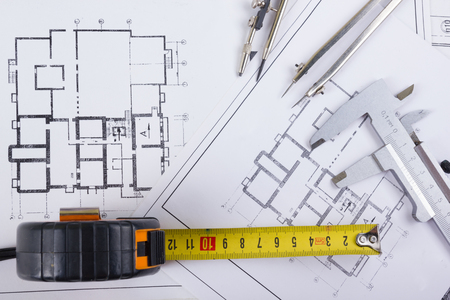 architecture design: Workplace of architect - Architectural project, blueprints, rolls and tablet, pen, divider compass on plans. Engineering tools view from the top. Construction background. Copy space for text