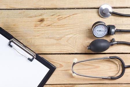 医療のクリップボードと木製のデスクの背景に聴診器。平面図です。医師の職場