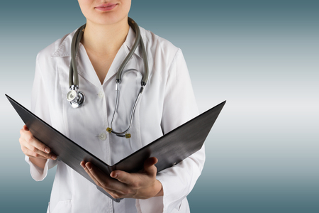 taking inventory: Female doctors hand holding stethoscope and clipboard on blue blurred background. Concept of Healthcare And Medicine. Copy space. Stock Photo