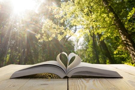 Libro aperto sul tavolo di legno su sfondo sfocato naturale. pagina del libro Cuore. Di nuovo a scuola. Copiare lo spazio.