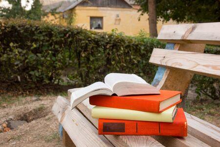 hardback: Stack of book and Open hardback book on blurred nature landscape backdrop. Copy space, back to school. Education background.