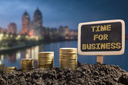 opportunity concept: Time For Business - Financial opportunity concept. Golden coins in soil Chalkboard on blurred urban background.