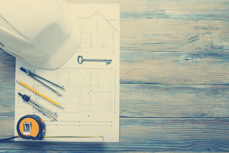 house blueprint: Architect worplace top view. Architectural project, blueprints, blueprint rolls and  divider compass, calipers on vintage wooden desk table. Construction background. Engineering tools. Copy space.