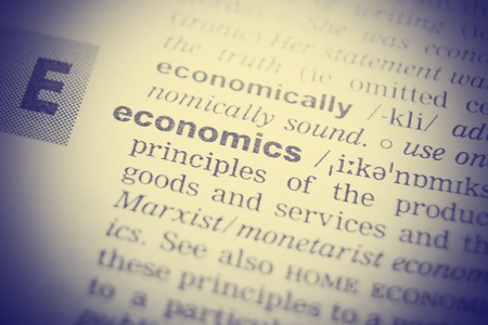 transcription: Close-up of word in English dictionary. Economics, definition and transcription.