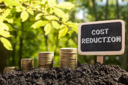 Cost reduction. Financial opportunity concept. Golden coins in soil Chalkboard on blurred urban background.