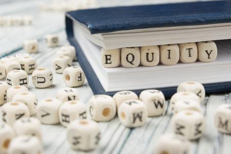 equity: EQUIDAD palabra escrita en el bloque de madera. Abc de madera.