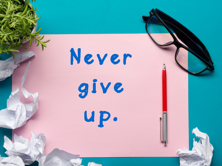 give up: Never give up message - Office desk table with supplies top view.  crumled paper, pen, glasses and flower Stock Photo