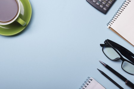 Office table with supply and coffe cup. View from above. Copy space for text. Stock Photo