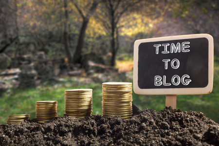 Time To Blog concept. Golden coins in soil Chalkboard on blurred natural background.