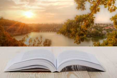 Open book on wooden table on natural blurred background.