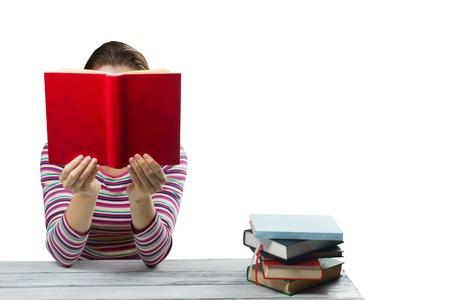 portadas de libros: Mujer joven que lee un libro y que cubre su rostro, sentado en la mesa de madera con pila de libros de tapa dura de colores aislados sobre fondo blanco. Foto de archivo
