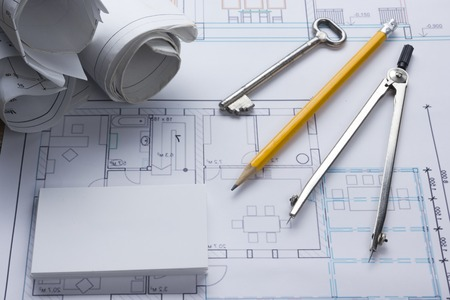 architect tools: Architect worplace top view. Architectural project, blueprints, blueprint rolls and  divider compass, key, blank business card on plans. Construction background. Engineering tools. Copy space.