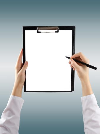 female hand holding a pen and clipboard with blank paper or document, report on blue blurred background. Top view.