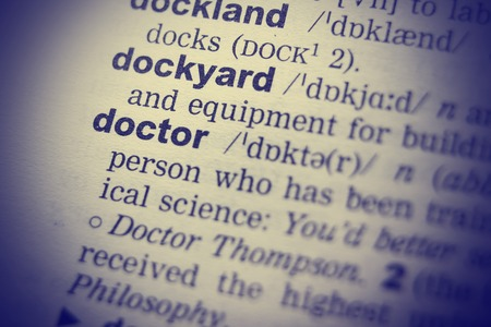 terminology: Close-up of word in English dictionary. Doctor definition and transcription