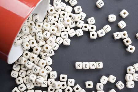 newspaper stack: Wood blocks with  letters spelling news. Wooden ABC
