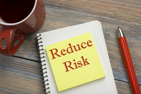 exploit: Risk management strategies - avoid, exploit, transfer, accept, reduce, ignore. Office desk table with notebook, pen and cup of coffee. Stock Photo