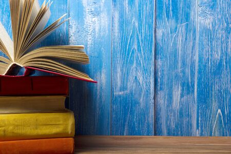 book stack: Open book, hardback books on wooden table. Back to school. Copy space for text.