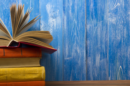 Open book, hardback books on wooden table. Back to school. Copy space for text.
