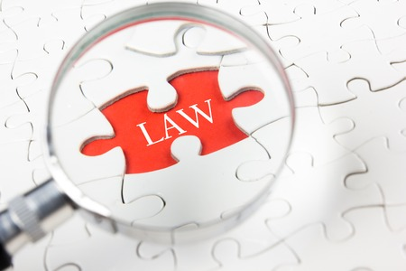 Law concept - Magnifying glass searching missing puzzle peace.