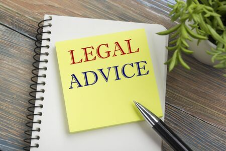 counsel: Legal Advice. Notepad with message, pen and flower. Office supplies on desk table top view.