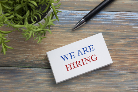 vacant sign: We are Hiring. Office desk table with business card, pen and flower. Top view Stock Photo