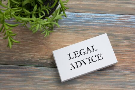 financial adviser: Legal Advice. Business card with message and flower. Office supplies on desk table top view. Stock Photo