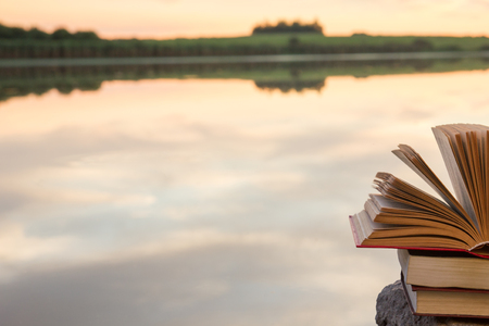 hardback: Stack of books and Open hardback book on blurred nature landscape backdrop against sunset sky with back light. Copy space, back to school. Education background Stock Photo