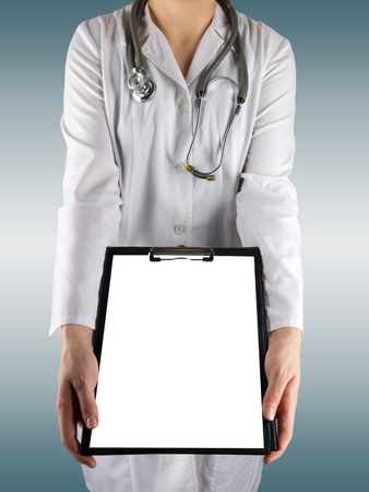 doctor s smock: Female doctors hand holding medical clipboard with blank sheet of paper and stethoscope on blue blurred background. Concept  Healthcare And Medicine. Copy space.
