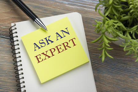 warranty questions: Ask an expert. Notepad with message, pen, reminder and flower. Office supplies on desk table top view Stock Photo