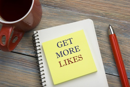 likes: Get More Likes concept. Notebook page with text, red pencil and coffee cup. Office desk table top view.