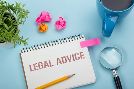 advising: Legal Advice. Notepad with message, coffee cup, pen and flower. Office supplies on desk table top view.