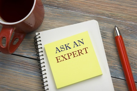 warranty questions: Ask an expert. Notepad with message, red pencil and coffee cup. Office supplies on desk table top view