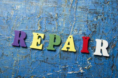 insurance claim: text of REPAIR on colorful wooden abc letter at abstract grunge blue background.