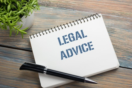 seeking assistance: Legal Advice. Notepad with message, pen and flower. Office supplies on desk table top view.