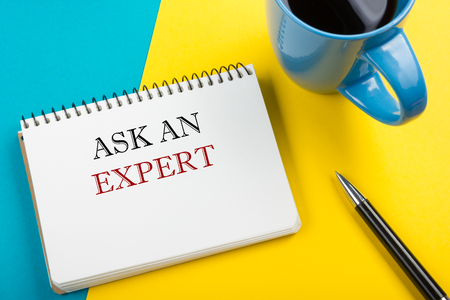 warranty questions: Ask an expert. Notepad with message, pen and coffee cup. Office supplies on desk table top view