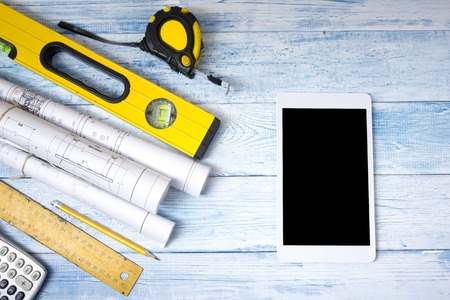 architect tools: Architect worplace top view. Architectural project, blueprints, blueprint rolls on wooden desk table. Construction background. Engineering tools. Copy space