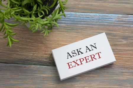warranty questions: Ask an expert. Business card with message. Office supplies on desk table top view