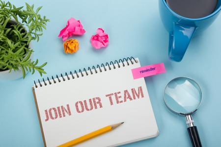 우리 팀에 합류하십시오. 메모장, 연필 및 커피 컵 사무실 책상 테이블. 평면도 스톡 콘텐츠