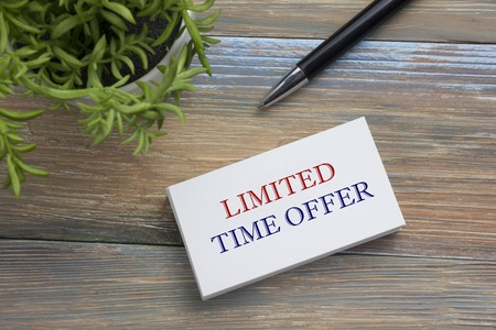 conditioned: Text Limited time offer on white paper book and office supplies on wooddesk. Business concept Stock Photo