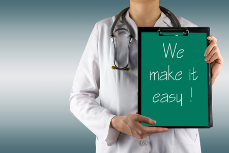 medical clipboard: We make it easy - Female doctors hand holding medical clipboard and stethoscope. Concept of Healthcare And Medicine. Copy space.