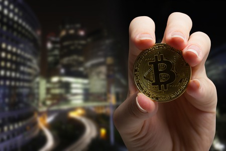 Cryptocurrency golden bitcoin coin. Hand holding symbol of crypto currency - electronic virtual money for web banking and international network payment. Selective focus Фото со стока