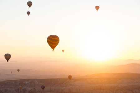 Hot air balloons over mountain landscape in Cappadocia, Goreme National Park, Turkey.