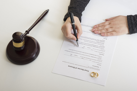 Hands of wife, husband signing decree of divorce, dissolution, canceling marriage, legal separation documents, filing divorce papers or premarital agreement prepared by lawyer. Wedding ring. Stockfoto