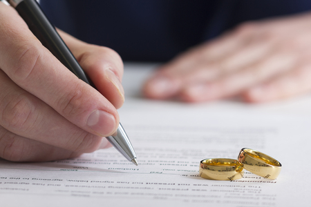 Hands of wife, husband signing decree of divorce, dissolution, canceling marriage, legal separation documents, filing divorce papers or premarital agreement prepared by lawyer. Wedding ring. 免版税图像