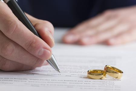 Ręce żony, męża podpisującego orzeczenie rozwodu, rozwiązania, unieważnienia małżeństwa, dokumentów separacji prawnej, złożenia dokumentów rozwodowych lub umowy przedmałżeńskiej przygotowanej przez prawnika. Pierścionek zaręczynowy.