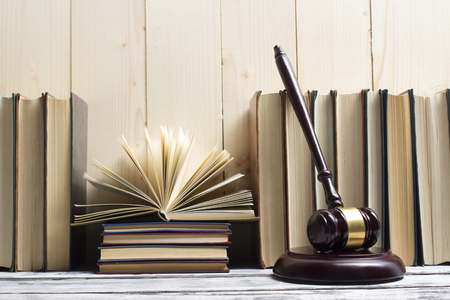 Legal Law concept - Open law book with a wooden judges gavel on table in a courtroom or law enforcement office. Copy space for text