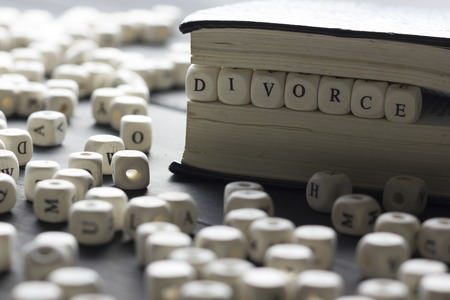 Word - Divorce made up of wooden letters on the table with wedding rings. 写真素材 - 97962056