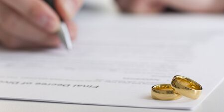 Divorce concept. Hands of wife, husband signing decree of divorce, canceling marriage, legal separation documents.