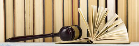 Legal Law concept - Open law book with a wooden judges gavel on table in a courtroom or law enforcement office. Stock Photo