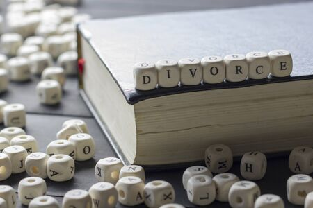 Word - Divorce made up of wooden letters on the table with wedding rings.